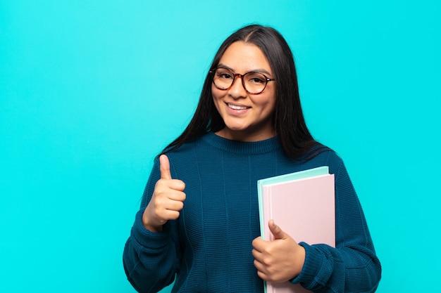 Junge lateinamerikanische frau, die breit lächelnd glücklich, positiv, selbstbewusst und erfolgreich aussieht, mit beiden daumen nach oben