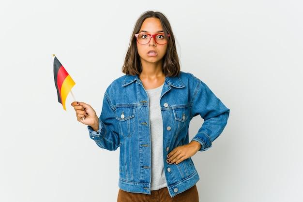 Junge lateinamerikanische frau, die eine deutsche fahne lokalisiert auf weißem raum hält, der wegen etwas geschockt wird, das sie gesehen hat.