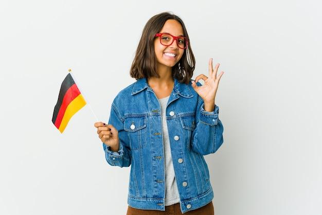 Junge lateinamerikanische frau, die eine deutsche flagge fröhlich und zuversichtlich hält, die ok geste zeigt.