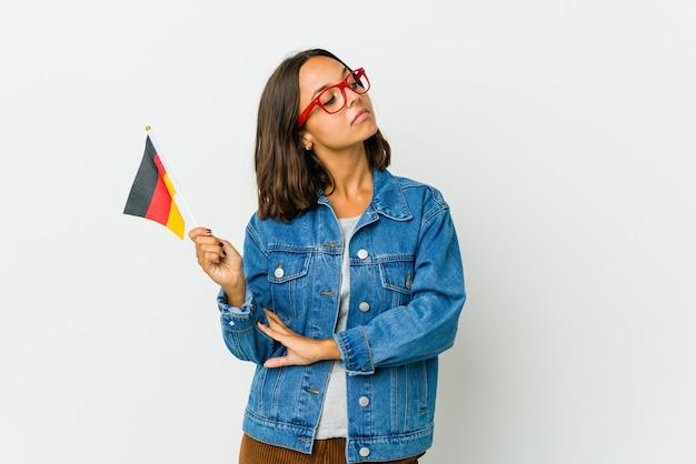 Junge lateinamerikanische frau, die eine deutsche flagge hält, die vom erreichen von zielen und zwecken träumt