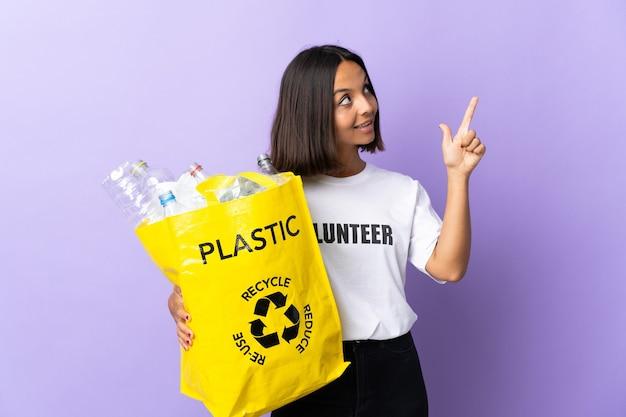 Junge lateinamerikanische frau, die einen recyclingbeutel voll papier hält, um isoliert auf lila zu recyceln, das mit dem zeigefinger eine große idee zeigt