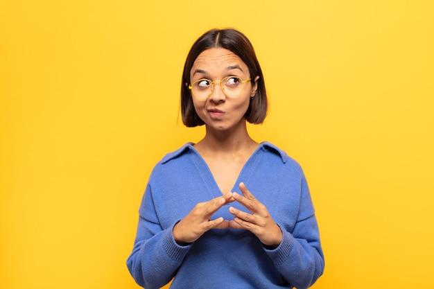 Junge lateinamerikanische frau, die entwirft und verschwört, verschlagene tricks und betrüger denkt, gerissen und verrät