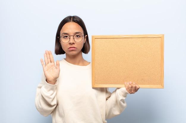Junge lateinamerikanische frau, die ernst, streng, unzufrieden und wütend aussieht und offene handfläche zeigt, die stoppgeste macht