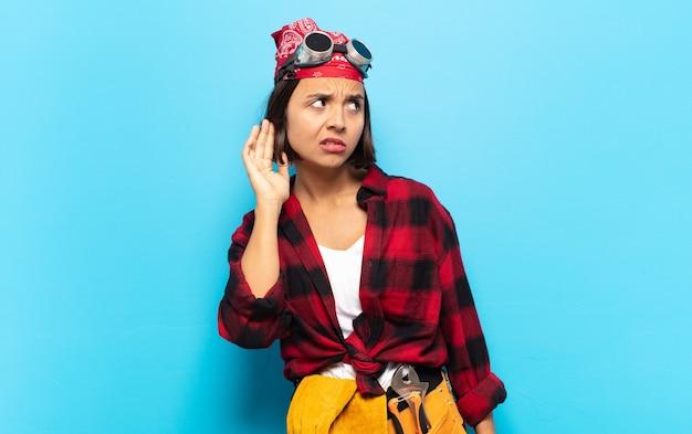 Junge lateinamerikanische frau, die ernst und neugierig aussieht, zuhört, versucht, ein geheimes gespräch oder klatsch zu hören, lauscht