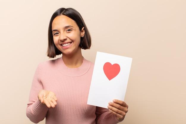 Junge lateinamerikanische frau, die glücklich mit freundlichem, selbstbewusstem, positivem blick lächelt und ein objekt oder konzept anbietet und zeigt