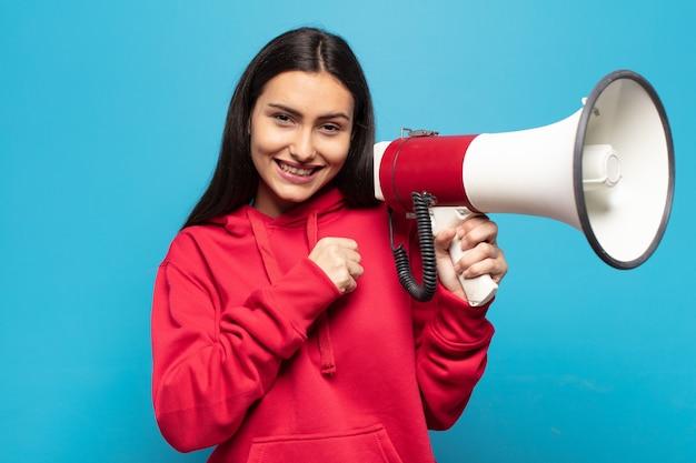 Junge lateinamerikanische frau, die glücklich, positiv und erfolgreich fühlt, motiviert, wenn sie sich einer herausforderung stellt oder gute ergebnisse feiert
