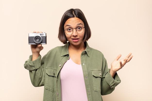Junge lateinamerikanische frau, die glücklich, überrascht und fröhlich fühlt, mit positiver einstellung lächelt und eine lösung oder idee verwirklicht