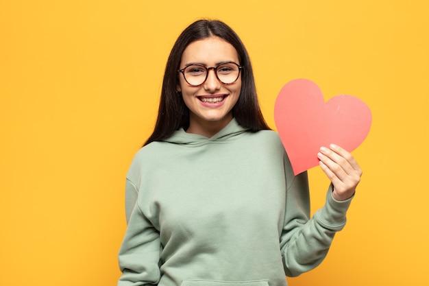 Junge lateinamerikanische frau, die glücklich und angenehm überrascht aussieht, aufgeregt mit einem faszinierten und schockierten ausdruck