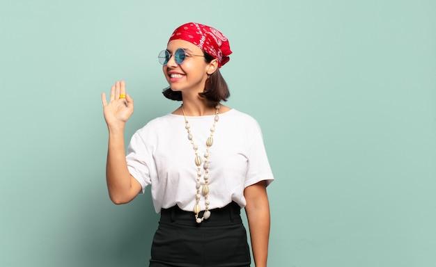 Junge lateinamerikanische frau, die glücklich und fröhlich lächelt, hand winkt, sie begrüßt und begrüßt oder sich verabschiedet