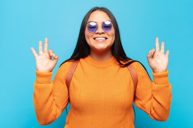 Junge lateinamerikanische frau, die konzentriert und meditierend aussieht, sich zufrieden und entspannt fühlt, denkt oder eine wahl trifft