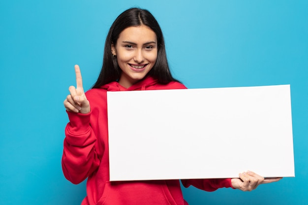 Junge lateinamerikanische frau, die lächelt und freundlich schaut, nummer eins oder zuerst mit der hand vorwärts zeigend, herunterzählend