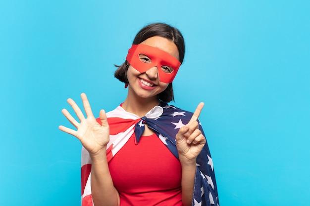 Junge lateinamerikanische frau, die lächelt und freundlich schaut, nummer sechs oder sechste mit der hand vorwärts zeigend, herunterzählend