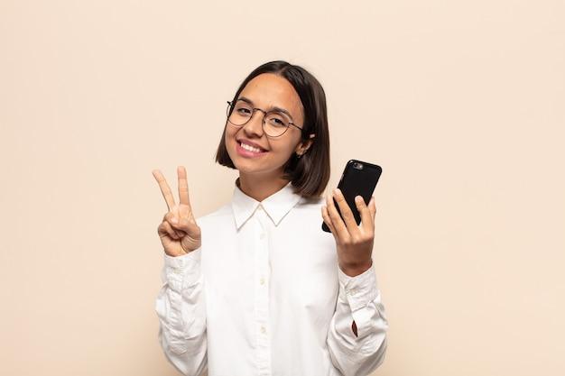 Junge lateinamerikanische frau, die lächelt und freundlich schaut, nummer zwei oder sekunde mit der hand vorwärts zeigend, herunterzählend