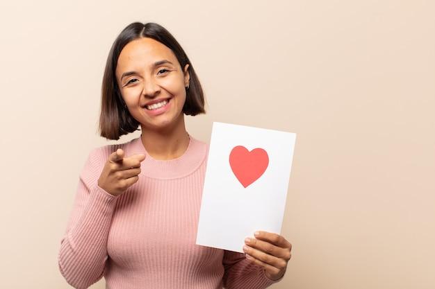 Junge lateinamerikanische frau, die mit einem zufriedenen, selbstbewussten, freundlichen lächeln auf kamera zeigt und sie wählt