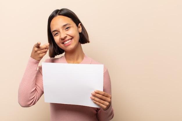 Junge lateinamerikanische frau, die mit einem zufriedenen, selbstbewussten, freundlichen lächeln nach vorne zeigt und sie wählt