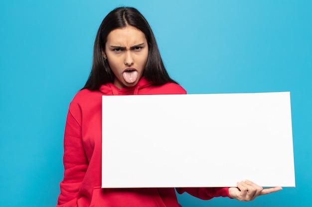 Junge lateinamerikanische frau, die sich angewidert und gereizt fühlt, die zunge herausstreckt und etwas böses und glückliches nicht mag