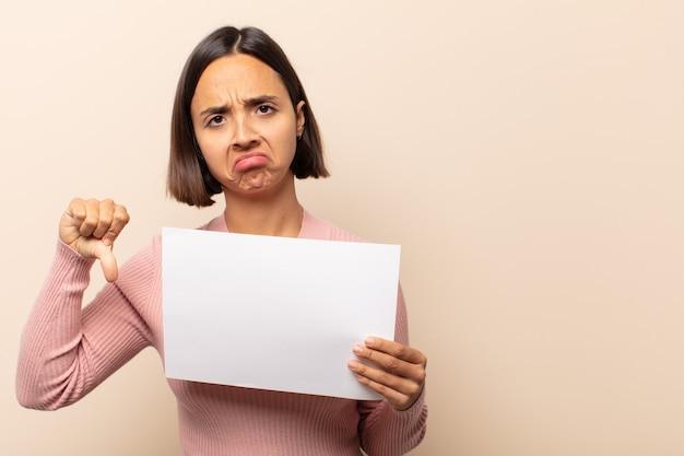 Junge lateinamerikanische frau, die sich böse, wütend, verärgert, enttäuscht oder unzufrieden fühlt und mit einem ernsten blick die daumen nach unten zeigt
