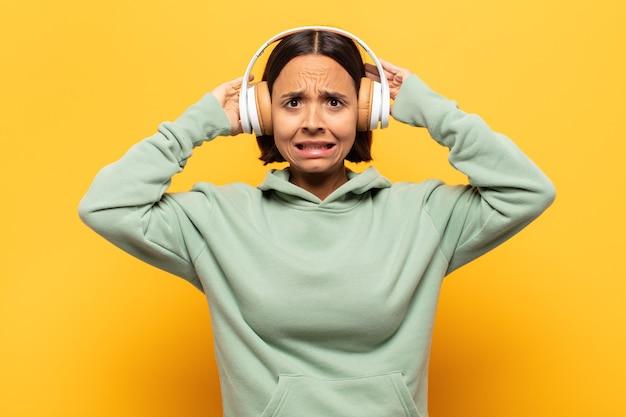 Junge lateinamerikanische frau, die sich gestresst, besorgt, ängstlich oder ängstlich fühlt, mit händen auf dem kopf, die bei einem fehler in panik geraten