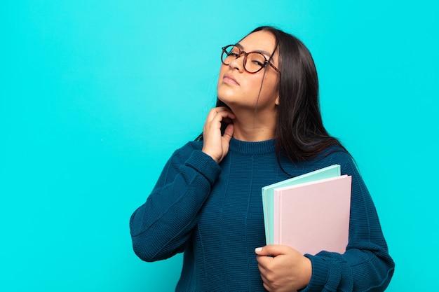 Junge lateinamerikanische frau, die sich gestresst, frustriert und müde fühlt und sich den schmerzhaften nacken reibt