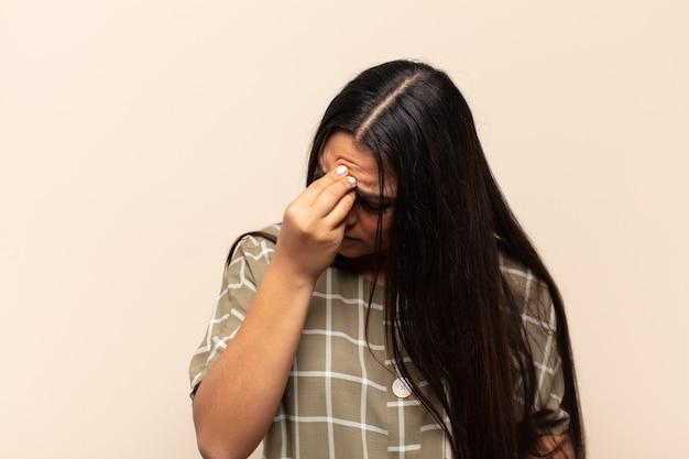 Junge lateinamerikanische frau, die sich gestresst, unglücklich und frustriert fühlt, die stirn berührt und unter migräne mit starken kopfschmerzen leidet