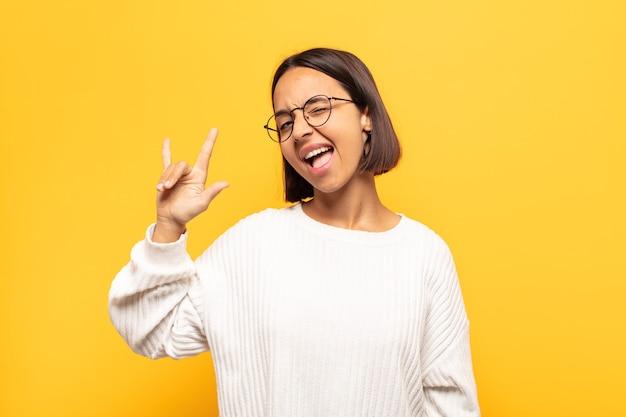 Junge lateinamerikanische frau, die sich glücklich, lustig, selbstbewusst, positiv und rebellisch fühlt und mit der hand rock- oder heavy-metal-schilder macht