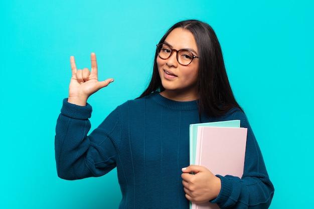 Junge lateinamerikanische frau, die sich glücklich, lustig, selbstbewusst, positiv und rebellisch fühlt und mit der hand rock- oder heavy-metal-zeichen macht