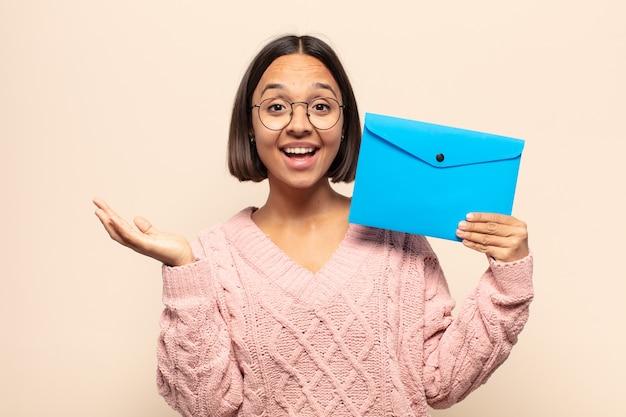 Junge lateinamerikanische frau, die sich glücklich, überrascht und fröhlich fühlt