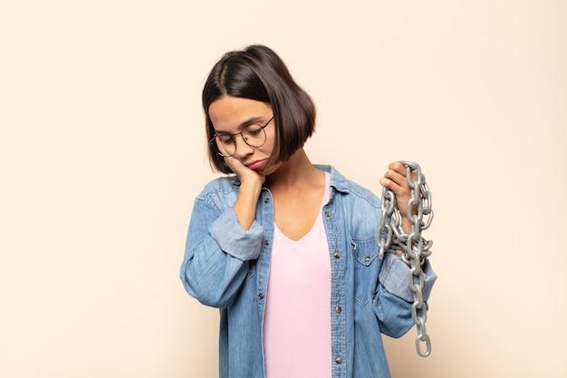 Junge lateinamerikanische frau, die sich nach einer ermüdenden, langweiligen und mühsamen aufgabe gelangweilt, frustriert und schläfrig fühlt und das gesicht mit der hand hält