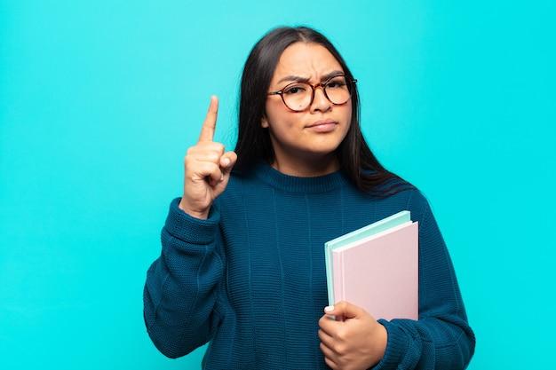 Junge lateinamerikanische frau, die sich wie ein genie fühlt, das stolz finger in der luft hält, nachdem sie eine große idee verwirklicht, eureka sagend