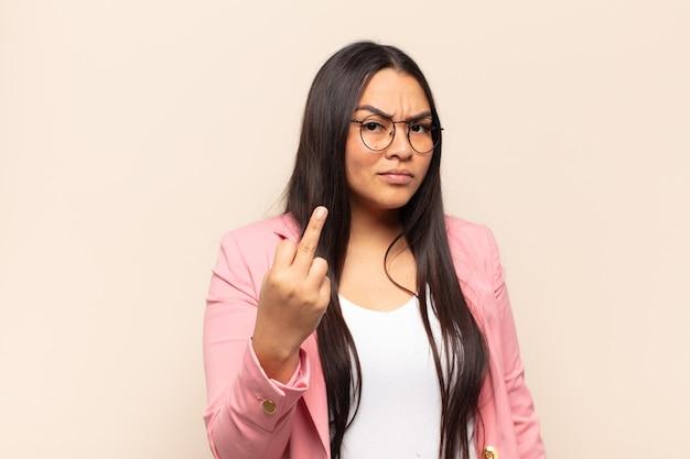 Junge lateinamerikanische frau, die sich wütend, verärgert, rebellisch und aggressiv fühlt, den mittelfinger umdreht und sich wehrt