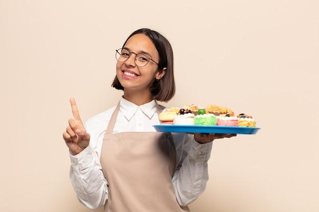 Junge lateinamerikanische frau, die stolz und zuversichtlich lächelt und nummer eins triumphierend posiert und sich wie ein anführer fühlt