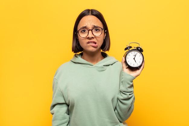 Junge lateinamerikanische frau, die verwirrt und verwirrt aussieht, mit einer nervösen geste auf die lippe beißt und die antwort auf das problem nicht kennt