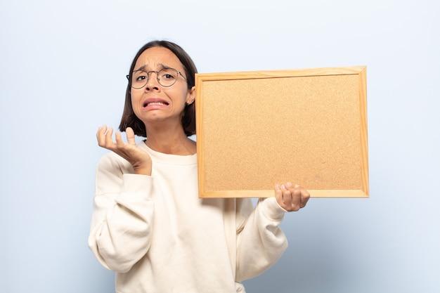 Junge lateinamerikanische frau, die verzweifelt und frustriert, gestresst, unglücklich und genervt aussieht, schreit und schreit