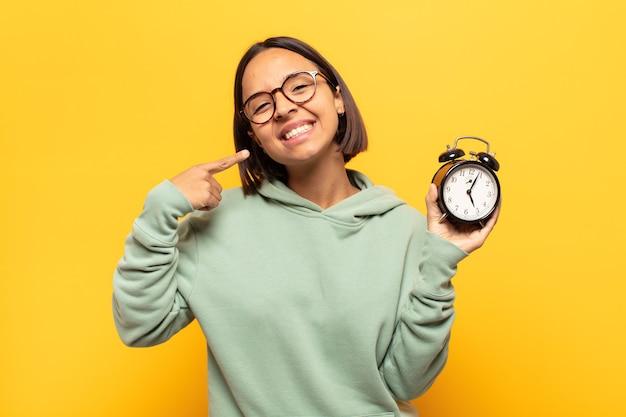 Junge lateinamerikanische frau, die zuversichtlich lächelt und auf eigenes breites lächeln, positive, entspannte, zufriedene haltung zeigt
