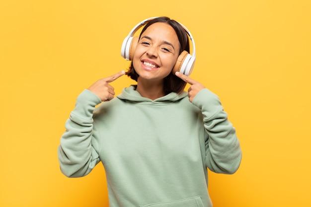 Junge lateinamerikanische frau, die zuversichtlich lächelt, zeigt auf eigenes breites lächeln, positive, entspannte, zufriedene haltung