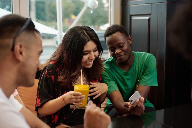 Junge lateinamerikanische frau lacht, während sie auf das telefon ihrer freundin schaut.