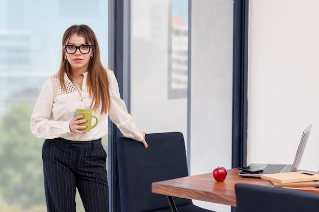 Junge lateinamerikanische frau mit einer tasse kaffee in der hand, die eine pause bei der arbeit zu hause macht