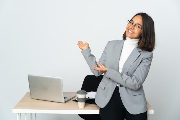 Junge lateinamerikanische geschäftsfrau, die in einem büro arbeitet, isoliert auf weißem hintergrund, das die hände zur seite ausstreckt, um einzuladen, zu kommen