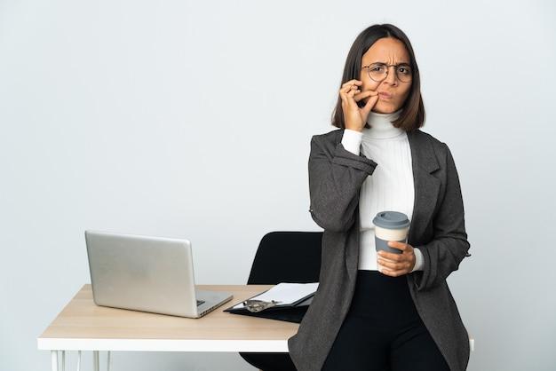 Junge lateinamerikanische geschäftsfrau, die in einem büro arbeitet, isoliert auf weißem hintergrund, das ein zeichen der stille zeigt