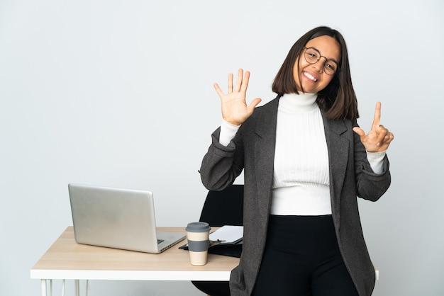 Junge lateinamerikanische geschäftsfrau, die in einem büro arbeitet, isoliert auf weißem hintergrund, das mit den fingern sieben zählt