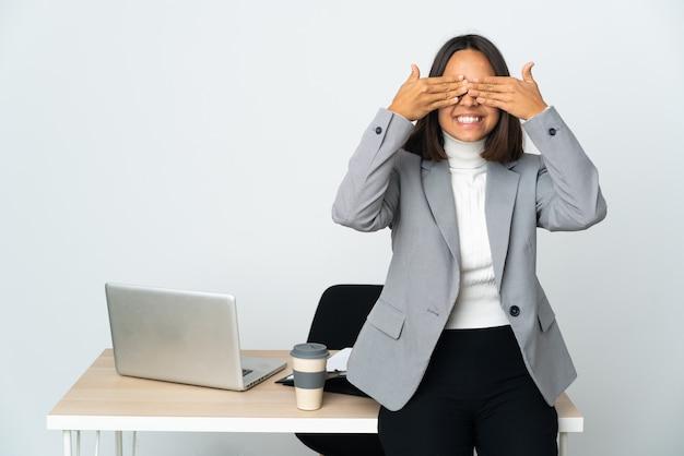 Junge lateinamerikanische geschäftsfrau, die in einem büro arbeitet, isoliert auf weißem hintergrund, die augen mit den händen bedeckt und lächelt