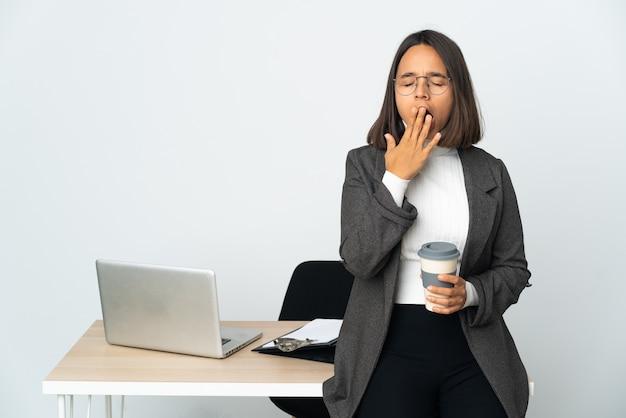 Junge lateinamerikanische geschäftsfrau, die in einem büro arbeitet, isoliert auf weißem hintergrund, gähnt und bedeckt den weit geöffneten mund mit der hand