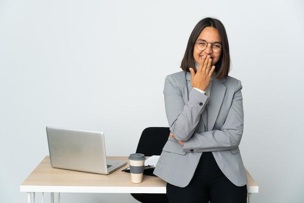 Junge lateinamerikanische geschäftsfrau, die in einem büro arbeitet, isoliert auf weißem hintergrund, glücklich und lächelnd, den mund mit der hand bedeckend