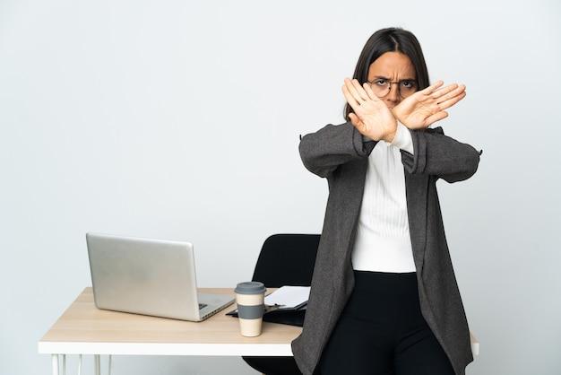 Junge lateinamerikanische geschäftsfrau, die in einem büro arbeitet, isoliert auf weißem hintergrund und mit der hand eine stoppgeste macht, um eine handlung zu stoppen?
