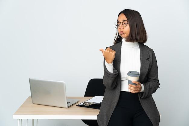 Junge lateinamerikanische geschäftsfrau, die in einem büro arbeitet, isoliert auf weißem hintergrund, unglücklich und zur seite zeigend