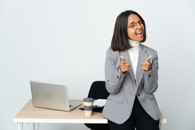 Junge lateinamerikanische geschäftsfrau, die in einem büro arbeitet, isoliert auf weißem hintergrund, zeigt nach vorne und lächelt