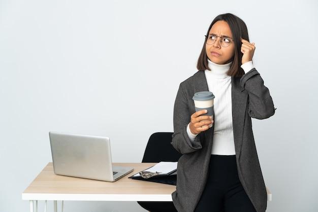 Junge lateinamerikanische geschäftsfrau, die in einem büro auf weißem hintergrund arbeitet und zweifel hat und denkt