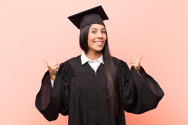Junge lateinamerikanische studentin, die freudig lächelt und glücklich aussieht, sich sorglos und positiv mit beiden daumen nach oben fühlend
