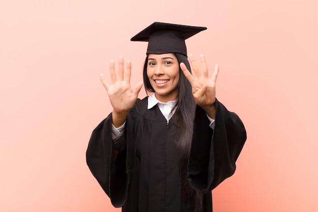 Junge lateinamerikanische studentin, die lächelt und freundlich aussieht und nummer neun oder neun mit der hand nach vorne zeigt und herunterzählt