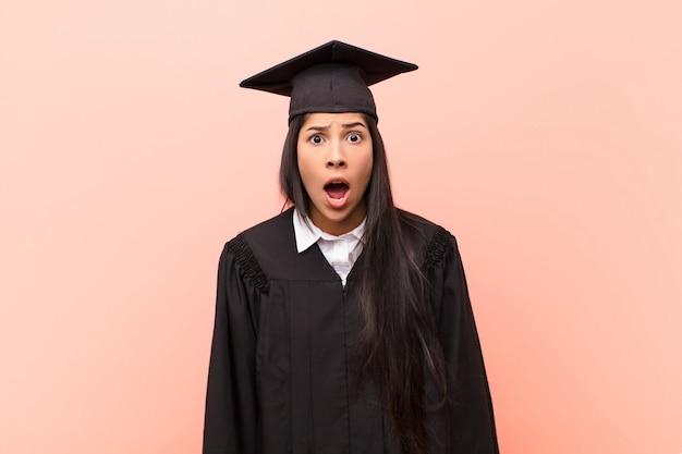 Junge lateinamerikanische studentin, die sich erschrocken und geschockt fühlt, mit offenem mund vor überraschung